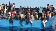 Dramatic footage captured by AFP shows a desperate rescue operation of hundreds of African migrants onboard an overcrowded wooden vessel found in...