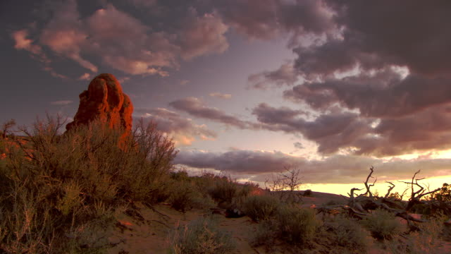 Dramatic rock formations in desert at sunset with beautiful sky - pan