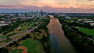 Dramatic Sunset Brings Colors to Texas Hill Country Downtown Austin Texas City Skyline Over Colorado River over Baseball Field