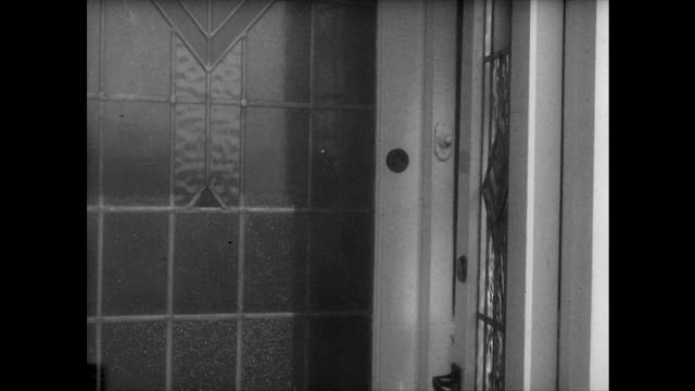 Dramatized sequence showing a person breaking into a suburban house