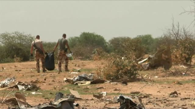 Dressed in protective white overalls French experts sift through the debris of the Air Algerie plane that disintegrated over the northern Mali desert...
