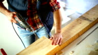 Drilling holes in a wood plank.