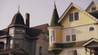 Drive by older homes w/ ornate architectural features on a residential street