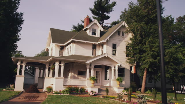 Drive by older homes with front porches on a residential street