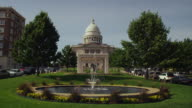 Drive by wide shot of Arkansas State Capitol building with water fountain in foreground