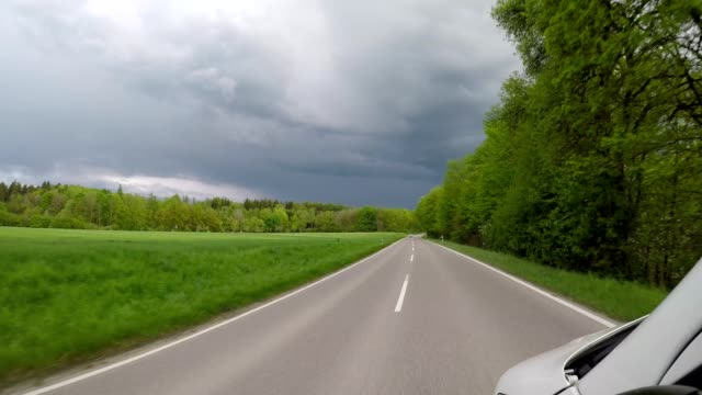 POV drive on country road in spring with stormy sky, Inning am Ammersee, Upper Bavaria, Bavaria, Germany