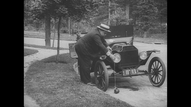 Driver Fatty Arbuckle accidently kicks passenger Buster Keaton in face before shrugging off encounter and focusing on his car