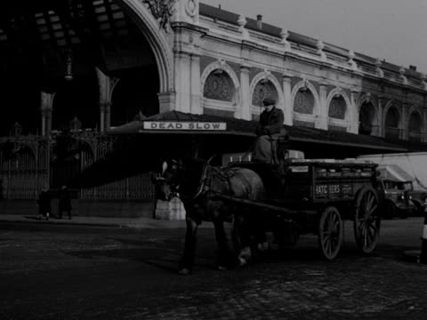 A driver leads a horse and cart past the entrance to Smithfield market 1953