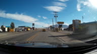 Driver pov of driving through a small town in the US