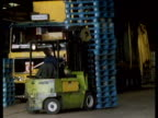Driver reverses fork lift truck carrying stack of empty blue pallets as other fork lift trucks whiz by in warehouse