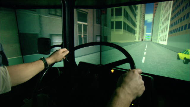 A driver steers a bus in a computer simulation.