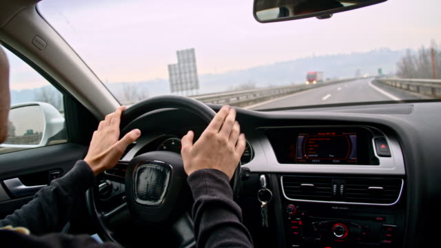 SLO MO Driver tapping with hands on a steering wheel