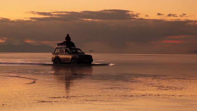 Driving across the flooded salar at sunset / Salar de Uyuni, Bolívia