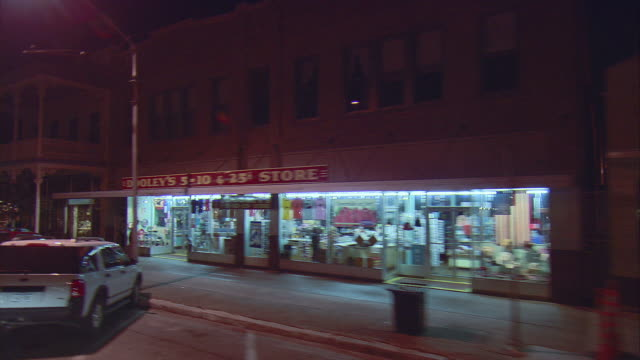 SIDE POV Driving along main street store fronts at night, Fredericksburg, Texas, USA