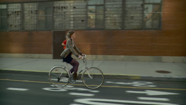 SIDE POV Driving down industrial street towards Williamsburg bridge, woman riding bicycle / New York City, New York, USA