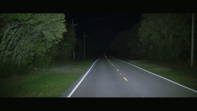 REAR POV Driving down rural two lane highway at night