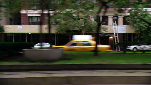 DS Driving in Midtown Manhattan, cruising past apartment buildings, school buses, and taxis on a divided avenue / New York City, New York, United States