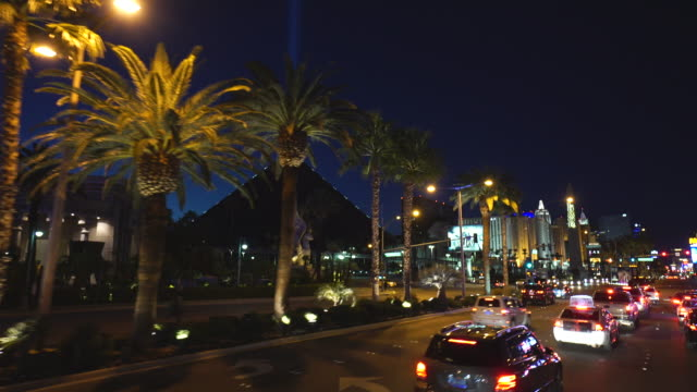 Driving POV of Las Vegas strip featuring the Luxor hotel at night