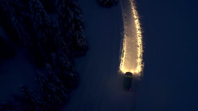 Fahren Sie auf die verschneiten Straße bei Nacht