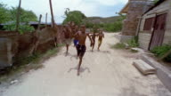 SLO MO, REAR POV, Driving on dirt road, group of boys (12-13, 13-14) following car, Santiago de Cuba, Cuba