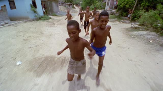 SLO MO, REAR POV, Driving on dirt road, group of boys (12-13, 13-14) following car, Santiago de Cuba, Cuba
