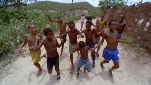 SLO MO, REAR POV, Driving on dirt road, group of children (12-13, 13-14) following car, Santiago de Cuba, Cuba