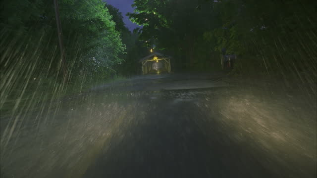 POV Driving on rural highway and through covered bridge in heavy rain at night