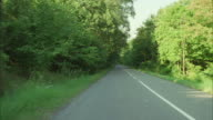 REAR POV Driving on rural tree lined road