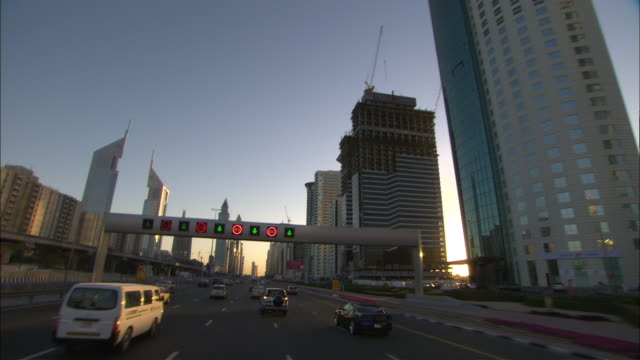 POV Driving on Sheik Zayed Road toward Jumeirah Emirates Hotel Towers and The Tower buildings at sunset, Dubai, United Arab Emirates