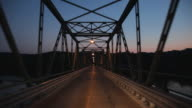 POV Driving on steel bridge over Delaware River at dusk / Frenchtown, New Jersey, USA
