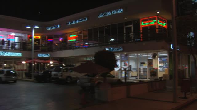 Driving past Sunset Boulevard businesses at night, passenger POV