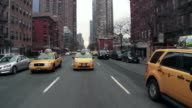 Driving Reverse POV of 10th Avenue between 43rd and 47th streets on a grey day.