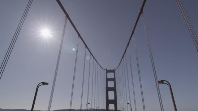 Driving shot of the Golden Gate Bridge midday , then Pan up pillar.