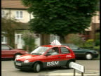 Young drivers C4N SAME ENGLAND London Wimbledon TMS British School of Motoring Vauxhall Corsa car along towards TRACK BACK as learner driver at the...