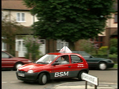 Young Drivers ENGLAND London Wimbledon TMS British School of Motoring Vauxhall Corsa car along towards TRACK BACK as learner driver at the wheel...
