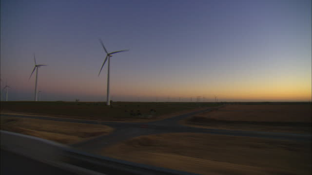 SIDE POV Driving through rural area with wind turbines at dusk, Sweetwater, Texas, USA
