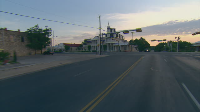 POV Driving through small town intersection at sunrise, Fredericksburg, Texas, USA