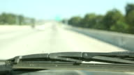 Driving. Transportation. View through vehicle windshield. Traveling down highway.