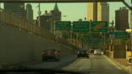 Driving westbound on bridge entering Manhattan various cars in lanes passing under green highway signs NYC