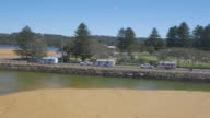 Drone aerial convoy of three utes towing caravans passes in front of Lakeside Caravan Park and over South Creek bridge Narrabeen