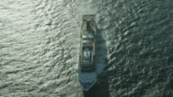 drone aerial cruise ship sailing on calm ocean seen from front sun glare on water drone flies over ship from bow to stern and over wake trail / low...