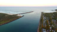 Drone aerial Hastings River entrance with Pelican Point and breakwater on left and Breakwall Caravan Park on right with Pacific Ocean ahead move...
