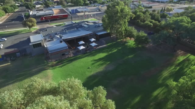 Drone aerial over Gol Gol Hotel and beer garden road train passes along Sturt Highway aka Adelaide St pan to Murray River riverside reserve circular...
