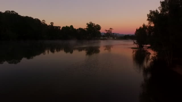 drone aerial starting low over Moruya River at dusk with pink twilight sky in background tracking along river with mist rising rising up to see...
