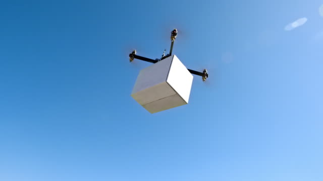 Drone carrying a box across the hills in sunshine