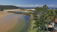 Drone low aerial of houses backing onto Narrabeen lagoon fronted by palm trees some with backyard pools / wide shot bridge in foreground beach in...