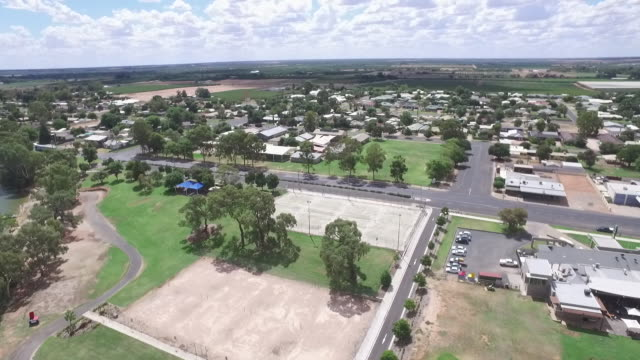 drone rises up over gum trees on Murray River Bank to wideshot river and surrounding district house boat cruises along zoom towards river boat zoom...