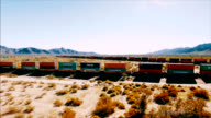 Drone shot revealing a moving container train barreling down a railroad in the middle of the American desert.