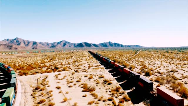 Drohne geschossen Tracking von links nach rechts über einen Container-Güterzug wie es unten eine Eisenbahn in der amerikanischen Wüste Fässer.