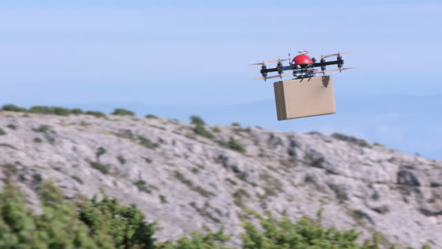 SLO MO TS Drone transporting package above the hilltops